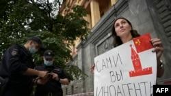 """Seorang jurnalis memegang poster yang bertuliskan """"Kamu lah yang agen asing"""" dalam sebuah gerakan solidaritas dengan sesama rekan media, yang baru saja dicap sebagai agen asing oleh pemerintah Rusia, di depan kantor Federal Keamanan Rusia pada 21 Agustus 2021. (Foto: AFP)"""
