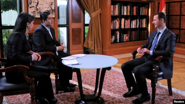 Syria's President Bashar al-Assad (R) attends an interview with Syrian television channel al-Ikhbariya in Damascus, in this handout photograph from Syria's national news agency SANA, April 17, 2013.