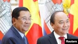 រូបឯកសារ៖ លោកនាយករដ្ឋមន្ត្រី ហ៊ុន សែន (ឆ្វេង) ថតរូបជាមួយនឹងលោកនាយករដ្ឋមន្ត្រីវៀតណាម ង្វៀន សួនហ៊្វុក (Nguyen Xuan Phuc) នៅការិយាល័យរដ្ឋាភិបាលវៀតណាម នៅទីក្រុងហាណូយ កាលពីថ្ងៃទី២០ ខែធ្នូ ឆ្នាំ២០១៦។ (REUTERS/Kham)