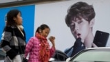 """FILE - Women walk past an ad featuring teen idol Lu Han in Beijing, Oct. 21, 2017. China's government banned effeminate men on TV and told broadcasters Sept. 2, 2021, to promote """"revolutionary culture."""""""