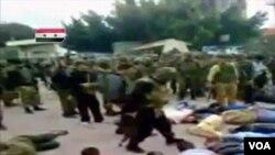 Gambar yang diambil dari kamera amatir ini memperlihatkan para tentara Suriah di Dara'a berjalan di antara warga sipil yang tiarap di aspal dan tangannya diikat, Selasa (3/5).