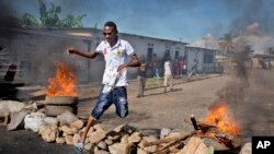 A civilian jumps over a burning barricade of rocks erected by residents to protect themselves from police, in a northern district of the capital Bujumbura, in Burundi, May 14, 2015.