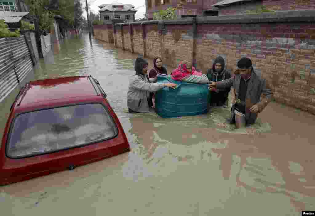 People transport a sick woman in an empty water tank on a flooded street during rain in Srinagar, Sept. 5, 2014.