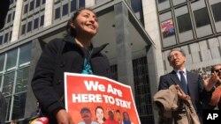"""旧金山法院大楼外,移民权利组织的抗议者手持标语""""我们要留在这里"""""""