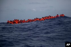 Migrants wait to be rescued in the Mediterranean Sea, about 15 miles north of Sabratha, Libya, July 25, 2017. French President Emmanuel Macron says processing asylum-seekers before their departure would save many from making the perilous journey.