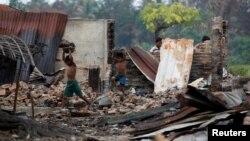 Anak anak Rohingya warga desa di pinggiran Maugndaw, negara bagian Rakhine mencari barang-barang dari rumah-rumah yang hangus dibakar akhir Oktober lalu (foto: dok).