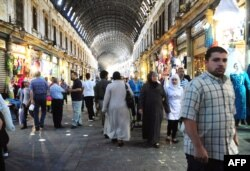 Syrians shop in the covered market in central Damascus as they prepare for the month of Ramadan, July 9, 2013.
