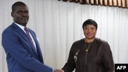 Sudan's Minister of Justice Nasruddin Abdel Bari, left, shakes hands with the International Criminal Court prosecutor Fatou Bensouda during her visit to the capital Khartoum on Oct. 18, 2020.