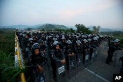 A wall of police in riot gear blocks the highway to stop a caravan of thousands of Central American migrants from advancing, outside Arriaga, Chiapas state, Mexico, Oct. 27, 2018.