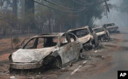 FILE - Burned cars left by their drivers sit along a road in Paradise, California after a wildfire burned much of the town in November of 2018.
