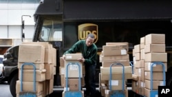 FILE - A UPS driver unloads packages from a truck and arranges them for delivery in New York.