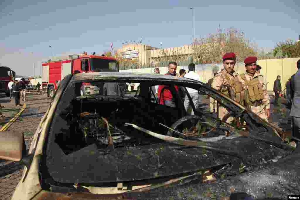 Kurdish security forces inspect the car used in the attack in Irbil, Nov. 19, 2014.