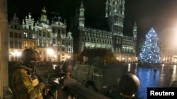 A Belgian soldier stands guard at the Grand Place of Brussels as police searched the area during a continued high level of security following the recent deadly Paris attacks, in Brussels, Belgium, Nov. 22, 2015.