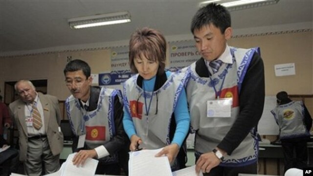 Members of local electoral committee sort through a ballot box, at a polling station in Bishkek, Kyrgyzstan, 10 Oct. 2010.