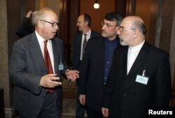 Iran's Ambassador to Finland Javad Kajoyan Fini and the Director of the Ministry of Foreign Affairs of Iran Hamid Baeidinejad (second from right) talk to the former chief U.N. Weapons inspector Hans Blix in Helsinki, April 7, 2005.