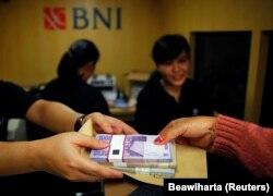 Seorang perempuan memegang uang kertas rupiah di salah satu bank keliling Bank Negara Indonesia (BNI) di Jakarta, 15 Juli 2013. (Foto: Reuters/Beawiharta)