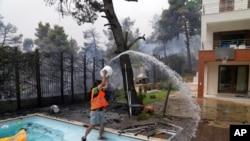 Afinanın təxminən 35 kilometr məsafədəki Ippokratios Politia kəndindəki evdə bir adam yaxınlaşan alova hovuzdan su atır