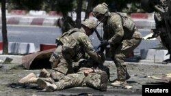 FILE - U.S. soldiers attend to a wounded soldier at the site of a blast in Kabul, Afghanistan June 30, 2015.