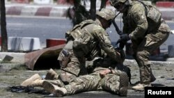 U.S. soldiers attend to a wounded soldier at the site of a blast in Kabul, Afghanistan June 30, 2015. (REUTERS/Omar Sobhani)