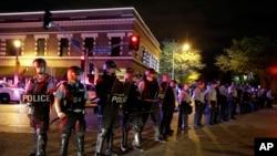Policías con trajes antimotines forman una línea de contención durante las protestas en San Luis, Missouri.
