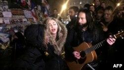 La chanteuse américaine Madonna, au centre, chante à côté de son guitariste Monte Pittman (à sa droite) et son fils David Banda (a gauche), au lieu de la République à Paris à un mémorial improvisé en hommage aux victimes des attaques terroristes à Paris, 10 décembre 2015.