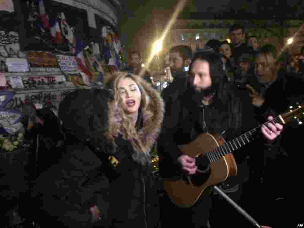 Singer Madonna (C) sings next to her guitarist Monte Pittman (C-R) and her son David Banda (L) at the place de la Republique in Paris at a makeshift memorial in tribute to victims of the Nov. 13 terror attacks in Paris.