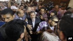 穆爾西(中)在開羅參加祈禱時在支持者中間。