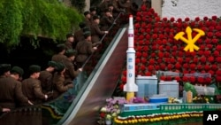 "North Korean soldiers ride escalator past a model of the Unha Rocket alongside so-called ""Kimjongilia"" flowers at an exhibition in Pyongyang, Feb. 17, 2013."