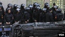 Polisi anti hura-hara Mesir berjaga-jaga di belakang sebuah mobil yang terbalik dan terbakar di luar gereja di Kairo.