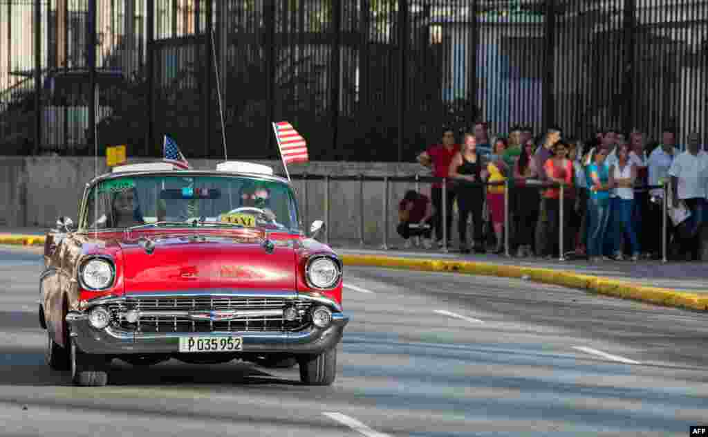 An old car with U.S. flags drives by the U.S. embassy in Havana. The United States and Cuba formally resumed diplomatic relations, as the Cuban flag was raised at the U.S. State Department in a historic gesture toward ending decades of hostility.
