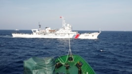 A ship (top) of the Chinese Coast Guard is seen near a ship of the Vietnam Marine Guard in the South China Sea, about 210 km (130 miles) off shore of Vietnam, May 14, 2014.