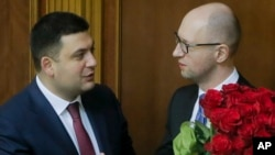 FILE - Prime Minister Arseniy Yatsenyuk, right, and parliament speaker Volodymyr Groysman are seen during the opening first session of the Ukrainian parliament in Kyiv, Nov. 27, 2014. Ukraine is looking to create a new coalition government this week following Yatsenyuk's resignation.