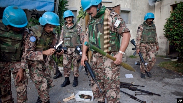 FILE - A U.N. peacekeeper collect weapons from the army headquarters of  Ivory Coast's strongman Laurent Gbagbo in Abidjan.