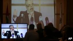 하마스 지도자 칼리드 마슈알이 1일 카타르 도하에서 가진 기자회견을, 가자시티의 하마스 관계자들이 중계화면으로 보고 있다.
