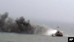 In this image provided by the Italian Navy, a helicopter hovers above the Italian-flagged Norman Atlantic, shown billowing smoke, after it caught fire in the Adriatic Sea, Dec. 28, 2014.