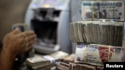 FILE - An employee counts money at an exchange office in downtown Cairo, Egypt.