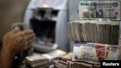 Un employé compte les billets dans un bureau de change au Caire, Egypte, le 5 juin 2014.