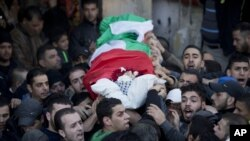 Palestinian mourners carry the body of Bilal Zayed, 23, who was killed in clashes with Israeli troops, during his funeral in the Qalandia refugee camp on the outskirts of the West Bank city of Ramallah, Thursday, Dec. 24, 2015.
