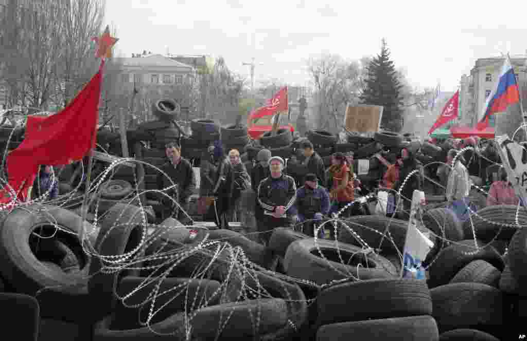 People stand at a barricade at the regional administration building that Moscow loyalists had seized earlier in Donetsk, Ukraine, April 15, 2014.