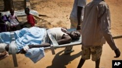 FILE - A man with a gunshot wound in his leg is carried by stretcher inside the Juba Military Hospital in Juba, South Sudan, Dec. 28, 2013.