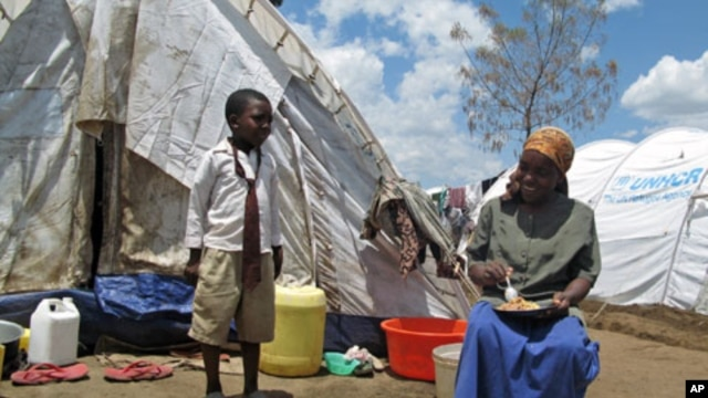 A boy talks to his mother, both internally-displaced persons, as she has lunch outside their temporary holding ground in Nakuru, Kenya, April 2008 (file photo)