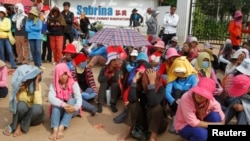 Workers gather during their strike in front of a factory owned by Sabrina (Cambodia) Garment Manufacturing in Kampong Speu province, west of the capital, Phnom Penh, May 30, 2013.