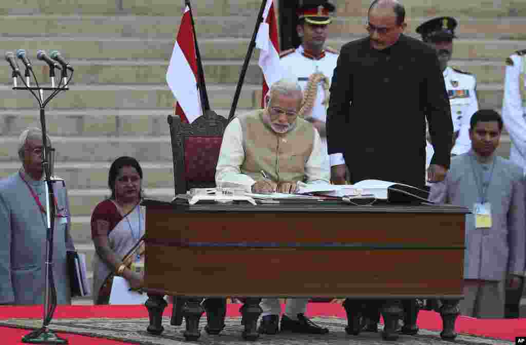 India's new prime minister Narendra Modi signs after taking the oath of office at the presidential palace in New Delhi, May 26, 2014.