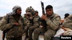 在叙利亚的库尔德人民保卫组织的武装人员抱着枪坐在小卡车里 (资料照片)