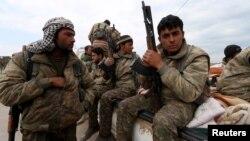 Các chiến binh Đơn vị Bảo vệ Người Kurd cầm vũ khí trong khi di chuyển trên một chiếc xe tải ở Qamishli, Syria, ngày 11/3/2016.