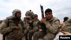 在叙利亚的库尔德人民保卫联盟的士兵手持武器坐在皮卡汽车上。(2016年3月11日)