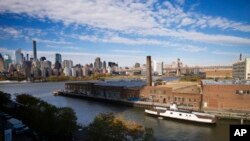 FILE- A rusting ferryboat is docked next to an aging industrial warehouse on Long Island City's Anable Basin in the Queens borough of New York. Amazon said on Feb. 14, 2019 that it will not be building a new headquarters in New York.