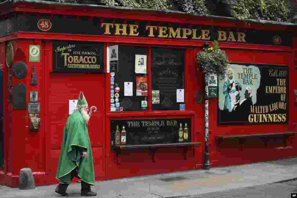 A man dressed as St. Patrick walks past a closed Temple bar in Dublin city center, Ireland.