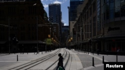 A pedestrian wearing a protective face mask crosses tram lines in the city center during a lockdown to curb the spread of COVID-19 in Sydney, Australia, 24, 2021.
