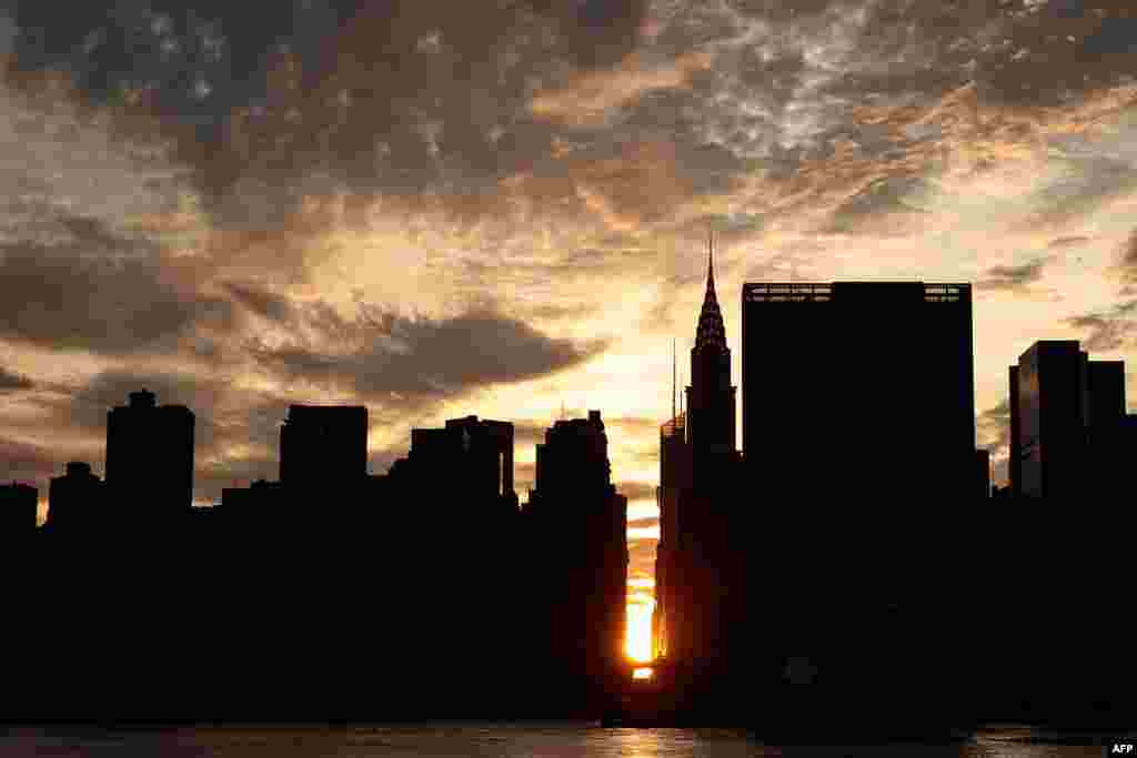 A view of the 'Manhattanhenge' sunset - setting sun aligns with the city's street grid - from Hunters Point South Park, in the Queens borough of New York City, July 11, 2016.